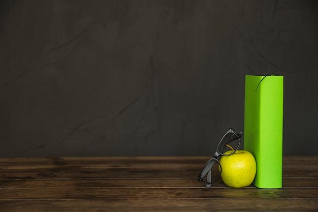 Luogo di lavoro con libro mela e occhiali