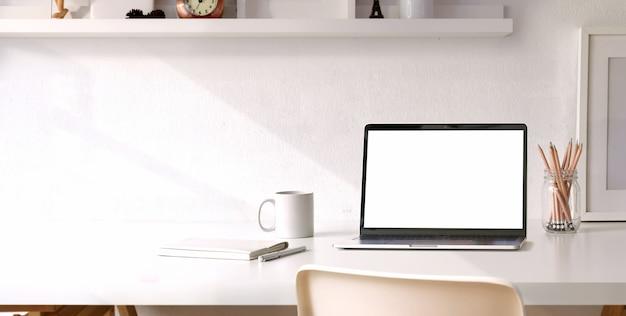 Luogo di lavoro confortevole con computer portatile schermo vuoto sul tavolo di legno bianco