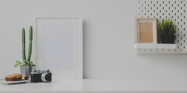 Luogo di lavoro confortevole con cornice mock up e copia dello spazio con la fotocamera