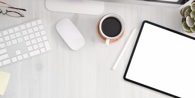 Luogo di lavoro confortevole con tablet schermo vuoto, forniture per ufficio e copia spazio sul tavolo di legno bianco