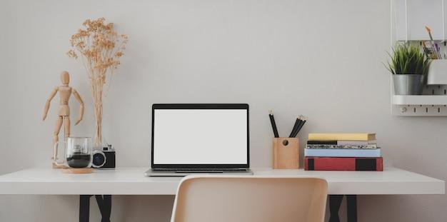 Luogo di lavoro contemporaneo con computer portatile schermo vuoto con libri e articoli per ufficio
