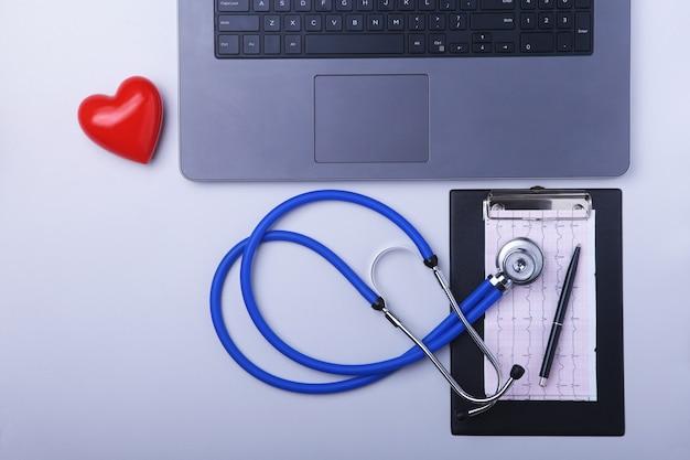 Luogo di lavoro del medico con laptop, stetoscopio, prescrizione rx e cuore rosso sul tavolo bianco.