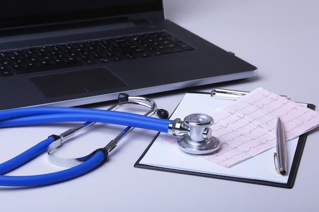 Luogo di lavoro del medico con laptop, stetoscopio, prescrizione rx e notebook sul tavolo.