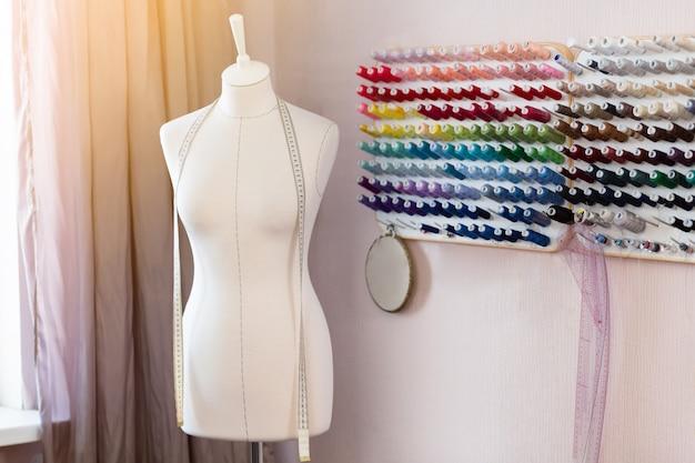 Luogo di lavoro di design con manichini cuciti, bobine con fili e metro a nastro.