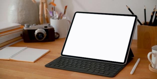 Luogo di lavoro di design con tavoletta digitale schermo vuoto e forniture per ufficio