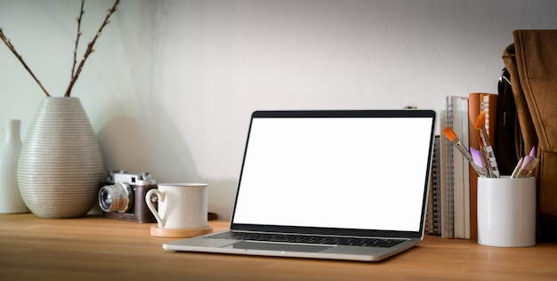 Luogo di lavoro di design confortevole con computer portatile schermo vuoto e forniture per ufficio