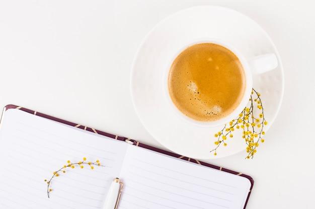 Luogo di lavoro di primavera con una tazza di caffè e un fiore di mimosa accanto a un blocco note aperto. vista dall'alto, piatta distesa