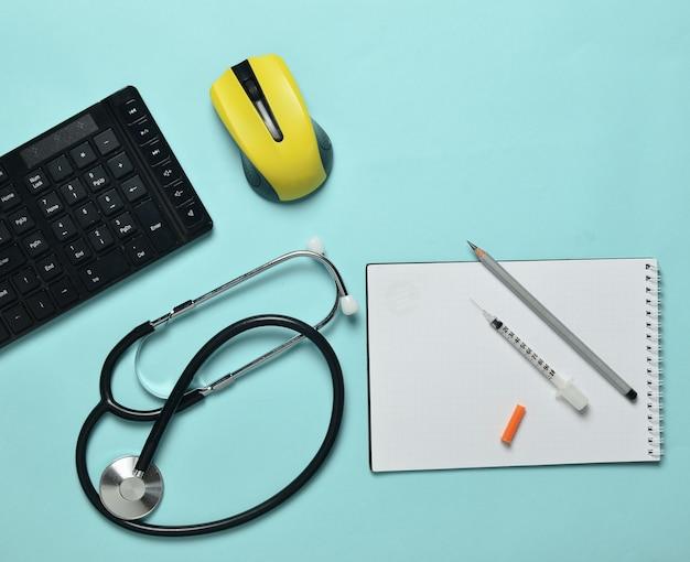 Luogo di lavoro di un medico moderno. tastiera, mouse wireless, notebook, stetoscopio, siringa su sfondo blu pastello, vista dall'alto, tendenza minimalista
