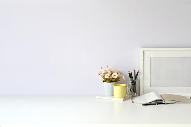 Luogo di lavoro e copia spazio, elegante area di lavoro con poster mockup in bianco, libri vintage e pianta della casa.