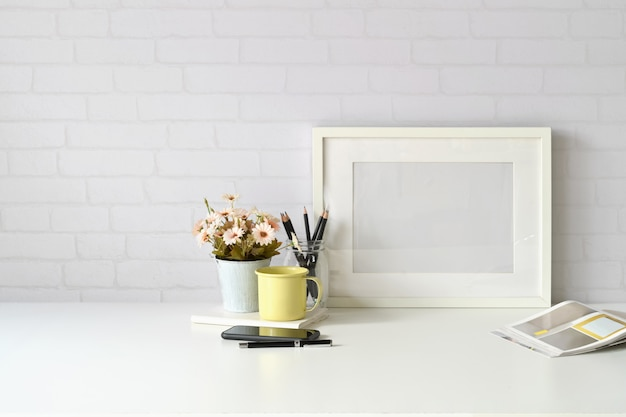 Luogo di lavoro e copia spazio, elegante area di lavoro con poster mockup, tazza di caffè e pianta di fiori.