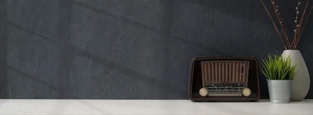Luogo di lavoro elegante e scuro con cornice mock up, radio vintage e decorazioni