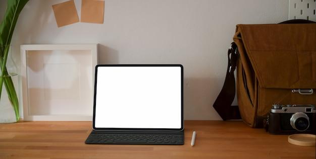Luogo di lavoro fotografo professionale con tablet schermo vuoto e forniture per ufficio