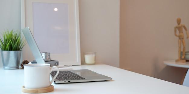 Luogo di lavoro minimo con computer portatile e una tazza di caffè