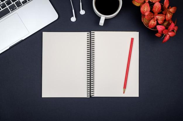 Luogo di lavoro minimo con laptop e blocco note vuoto