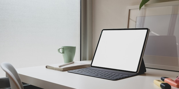 Luogo di lavoro minimo e confortevole con tablet con schermo vuoto