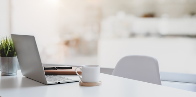 Luogo di lavoro moderno con computer portatile, tazza di caffè e articoli per ufficio