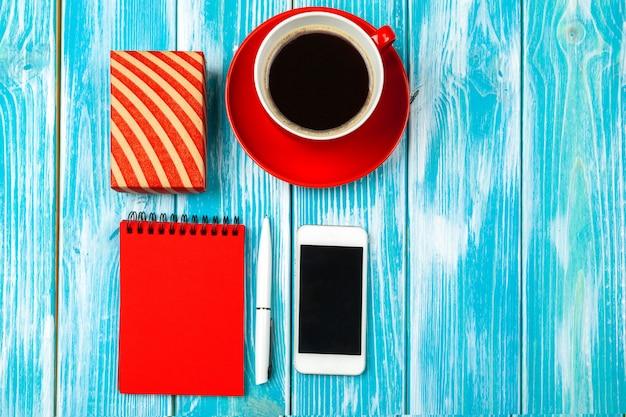 Luogo di lavoro moderno con la tazza di caffè sulla tavola di legno