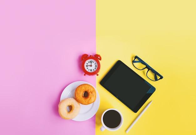 Luogo di lavoro, sveglia, caffè, ciambelle e tablet su sfondo pastello con spazio di copia