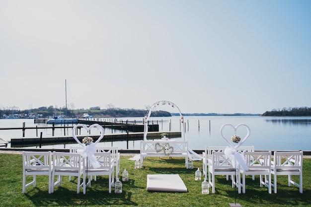 Luogo luogo per la cerimonia di nozze in riva al mare. sedie bianche e arco solenne