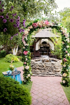 Luogo romantico con arco floreale e fontana realizzata in pietre nel giardino.
