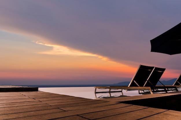 Lussuosa piscina a sfioro con solarium e terrazza molto bella e rilassante con cielo al tramonto