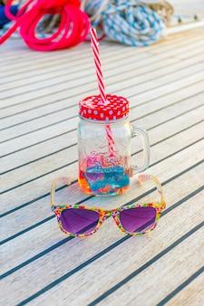 Lussuosi bicchieri viola e un'insolita tazza con una cannuccia si trovano sul ponte dello yacht durante il viaggio.