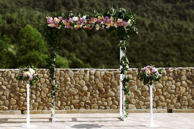 Lussuoso arco di nozze con foglie lussureggianti, rose delicate e ortensia viola all'aperto. floreale da cerimonia nuziale
