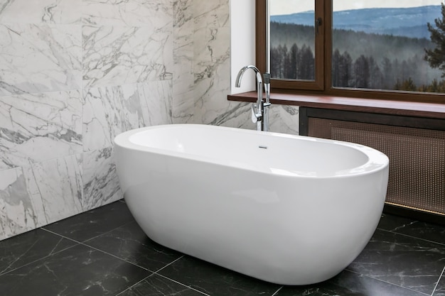 Lussuoso bagno con vasca indipendente in ceramica, pareti in marmo e finestra panoramica con vista sulla valle della foresta