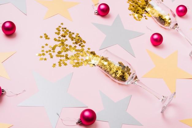 Lustrini di stelle sparsi dai bicchieri con palline lucenti