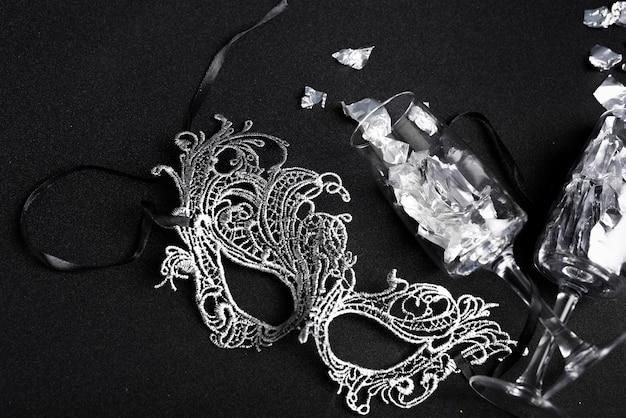 Lustrini sparsi dai bicchieri con la maschera sul tavolo