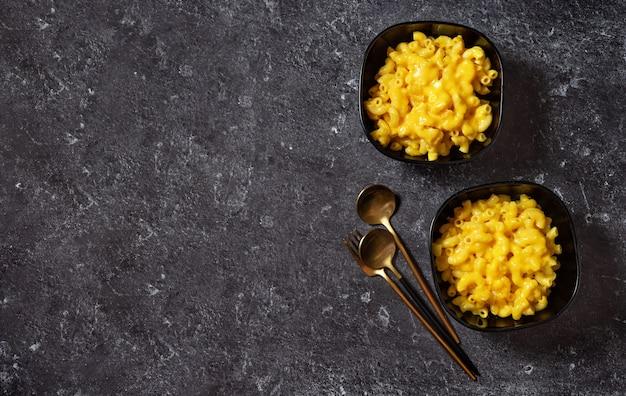 Mac e formaggio in due ciotole nere sul buio