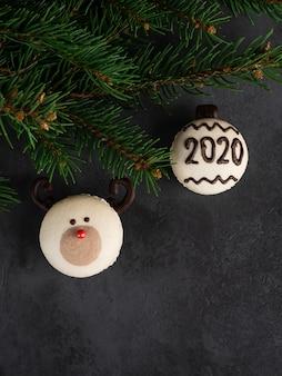 Macaron naso rosso renna e macaron con numero 2020 con abete brances su sfondo nero scuro. carta di natale e capodanno