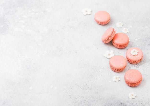 Macaron o maccherone rosa del dolce del dessert con i fiori dolci bianchi sulla cucina di pietra.