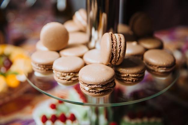 Macarons al cioccolato su uno scivolo di vetro per dessert