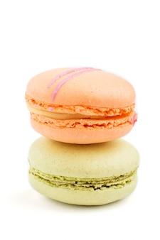 Macarons arancio e verdi o dolci dei maccheroni isolati, vista laterale.
