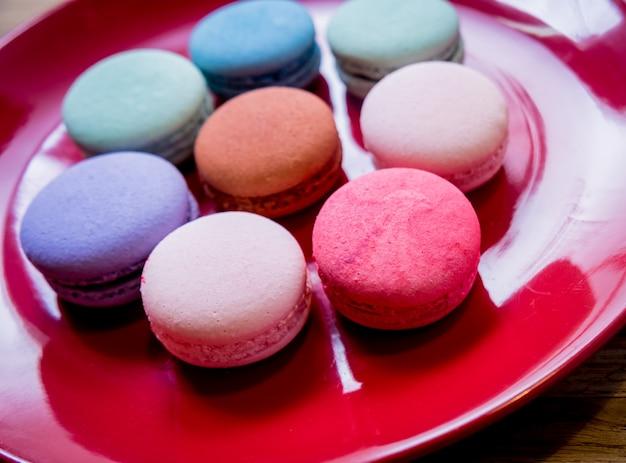 Macarons colorati francesi su un piatto rosso. ristorante.