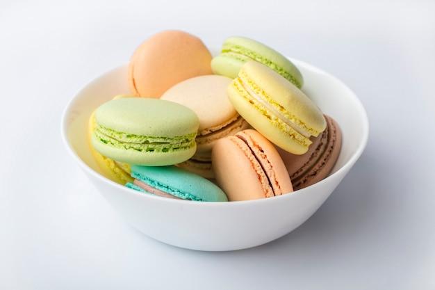 Macarons colorati nel piatto su uno sfondo chiaro
