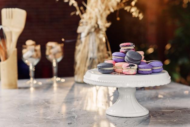 Macarons colorati su un vassoio bianco su un tavolo di marmo con un tovagliolo e accessori da cucina