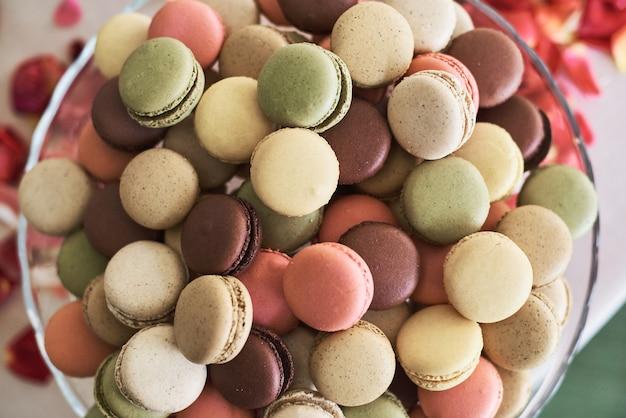 Macarons colorati su una lastra di vetro con petali rossi