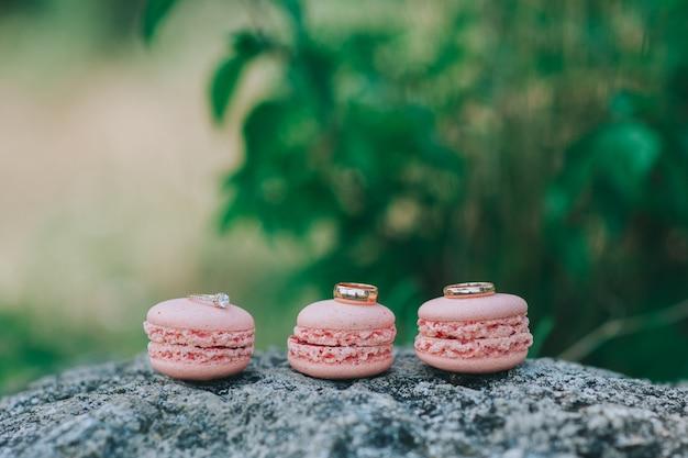 Macarons con il colpo alto vicino di fedi nuziali, retro filtro