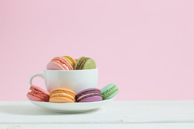 Macarons francesi variopinti in tazza su fondo di legno bianco.