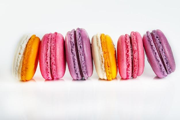 Macarons freschi di diversi colori e sapori isolati su bianco