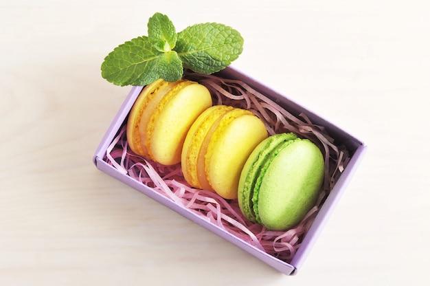 Macarons gialli e verdi della torta con la menta in scatola