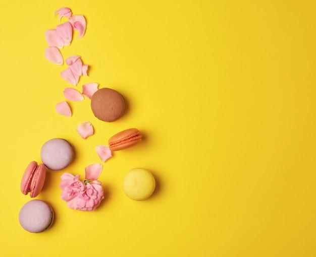 Macarons multicolori con crema e bocciolo di rosa rosa con petali sparsi