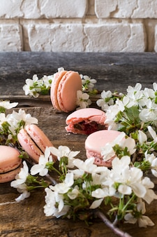 Macarons rosa con ganache al cioccolato, caramello e lampone. ramo fiorito dolce francese delicato maccheroni al lampone dolce nuziale primavera.