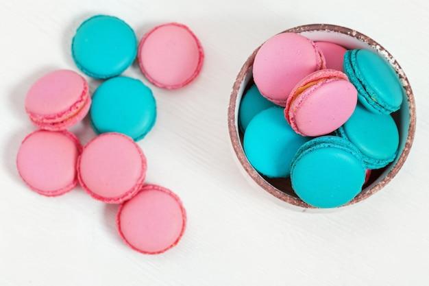 Macarons rosa e blu dei biscotti di mandorla in piatto sulla tavola di legno bianca con lo spazio della copia. dessert dolce croccante. vista dall'alto.