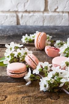 Macarons rosa, ganache al cioccolato, caramello, lampone. ramo fiorito dessert delicato