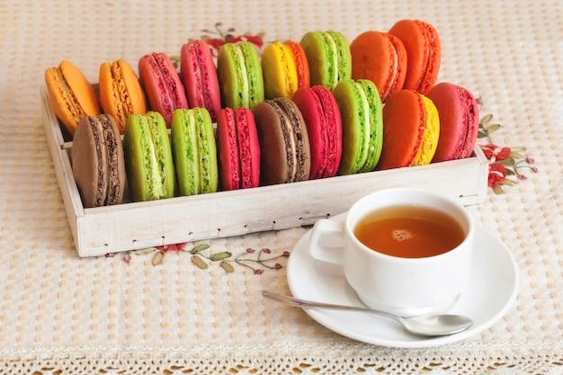 Macarons variopinti francesi tradizionali in una scatola, tazza di tè