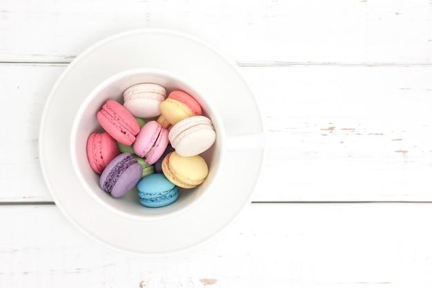Macarons variopinti in una tazza con pastello d'annata filtrato