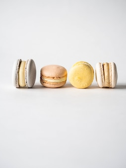 Macarons variopinti pastelli francesi freschi differenti su fondo bianco. copia spazio